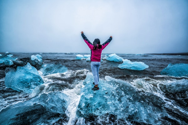 Young woman traveler travel to Diamond Beach in Iceland. Frozen ice on black sand beach known flows from Jokulsarlon beautiful Glacial Lagoon in Vatnajokull National Park, southeast Iceland, Europe.
