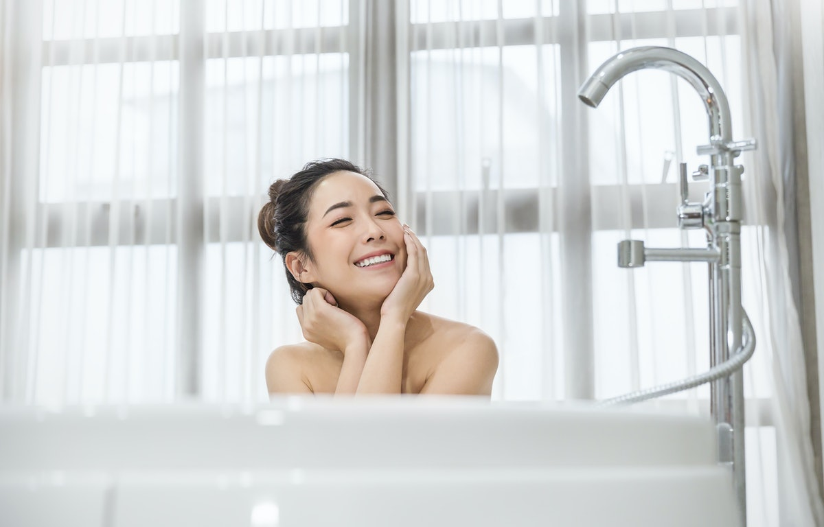 Portrait of young attractive happy asian girl takes a bath relax in the bathroom. Beauty woman in spa treatments. Healthy perfect glow skin care concept