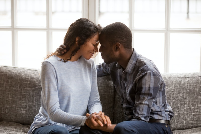 Black african married couple in love together at home. American woman and man embrace enjoy company of each other sitting on couch holding hands having romantic date. Feelings and first kiss concept