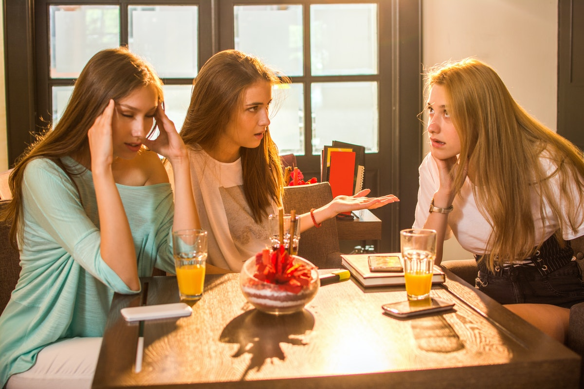 Angry, irritated teenage girlfriends arguing in cafe.