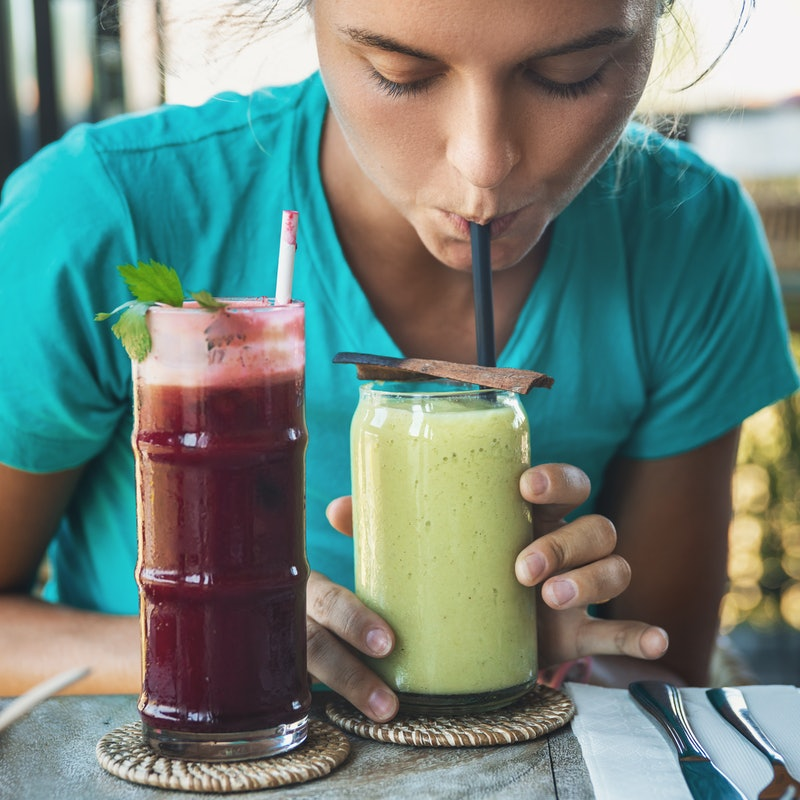 Woman is tasting different healthy drinks in vegan cafe. Avocado smoothie and beetroot juice.
