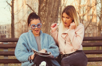 two young girl reading magazine and newspaper surprise and smiling news and horoscope friend time concept