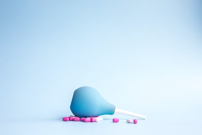 Blue douche lies and pills are pink and white around on a blue background. Women's health concept.