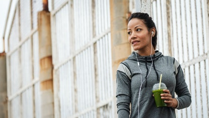 Happy urban fitness woman drinking detox green smoothie on a workout rest. Sport and modern healthy ...