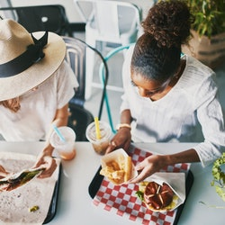 Two friends are eating a meal together at a restaurant. Comfort foods can be soothing to people living with chronic illness, especially during a flare.