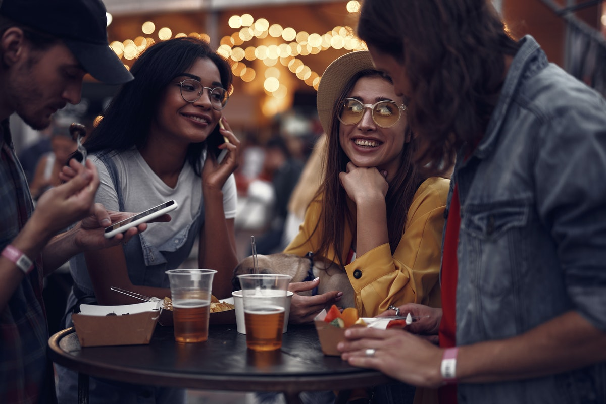 Portrait of young people standing at the table, chatting and using smartphones. Smiling girl in hat ...