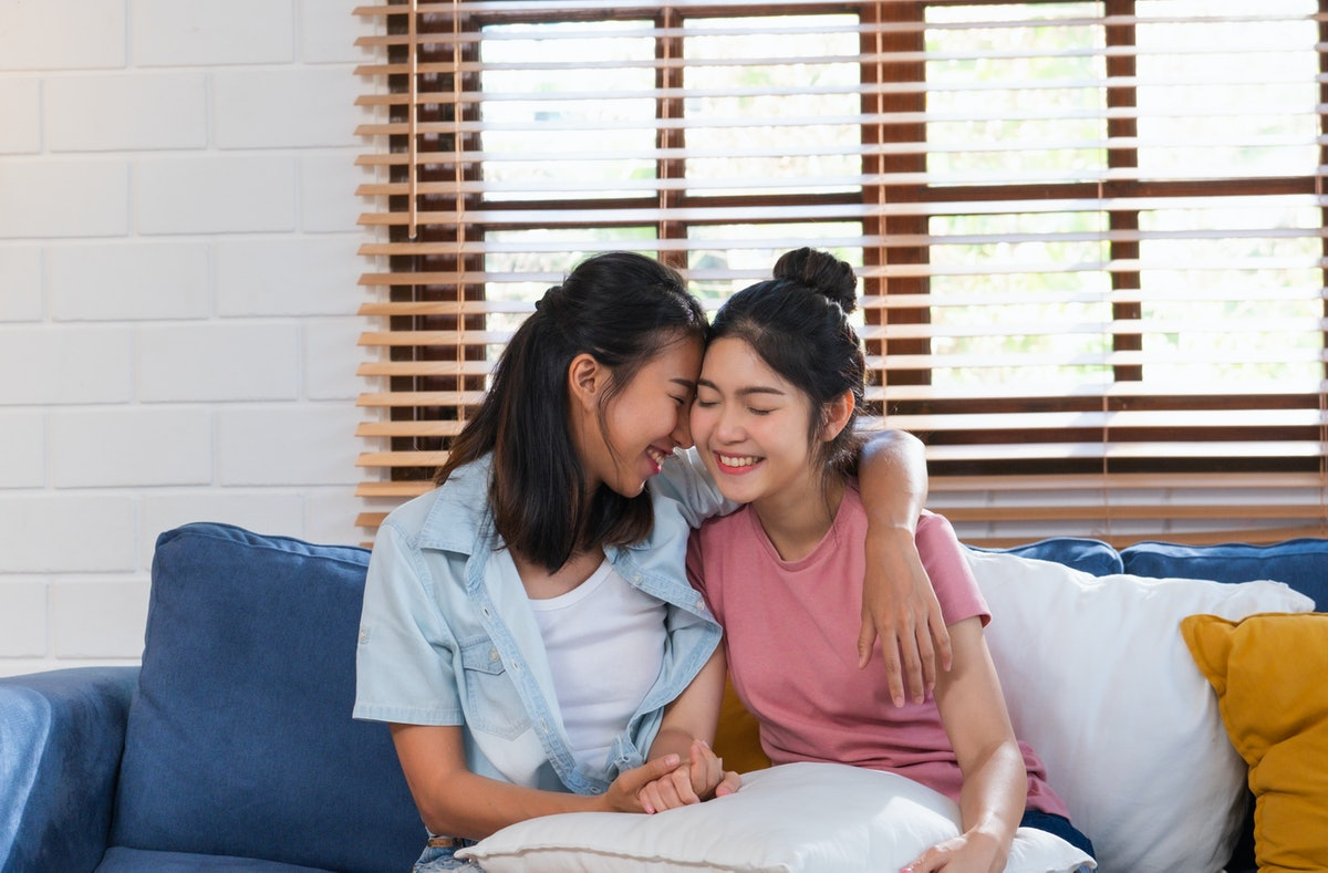 Happy asian lesbian couple hug each other with love on sofa at living room at home,LGBTQ lifestyle c...