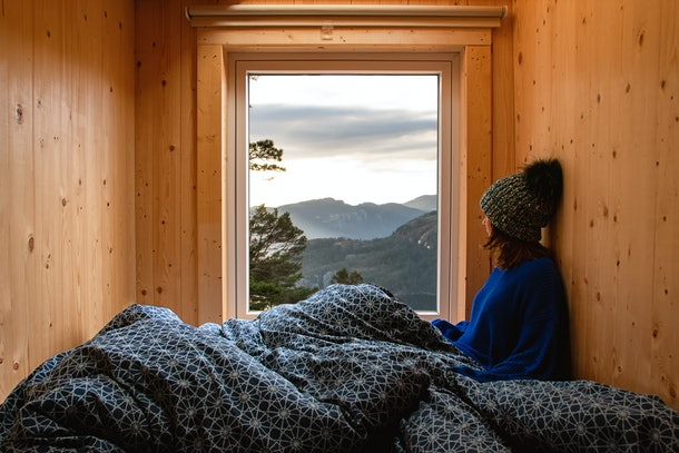 Adventure young girl in a wooden cabin glamping contemplating the landscape through the window