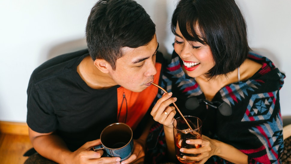 A young Malay couple snuggle up and share a hot beverage in their home. They are wrapped up and sitting on the floor and cosy as they talk to one another.