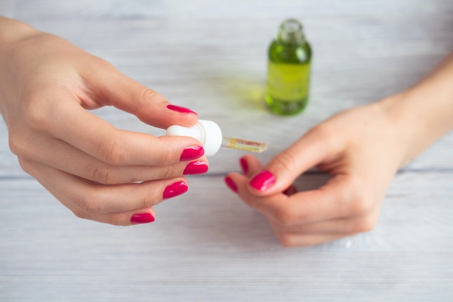 Female hands with pink manicure applied cosmetic oil on fingers