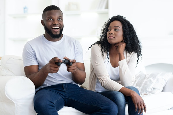 Boring date. Excited black guy rejoice winning in video game, annoyed tired and bored woman looking at him, free space
