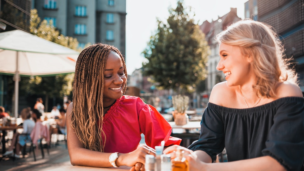 Happy female friends having fun at cafe, multi ethnic group of people hanging out in the city