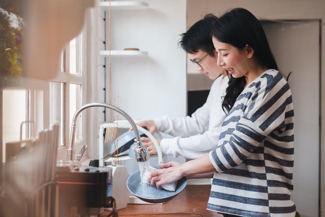 Asian couple family washing dishes together at kitchen