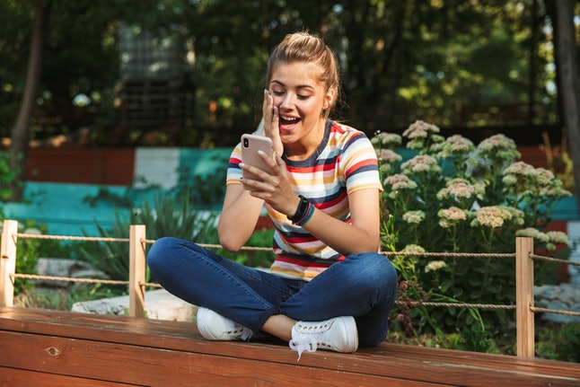 Portrait of a happy young teenage girl sitting on a bench at the park, looking a tmobile phone, laughing