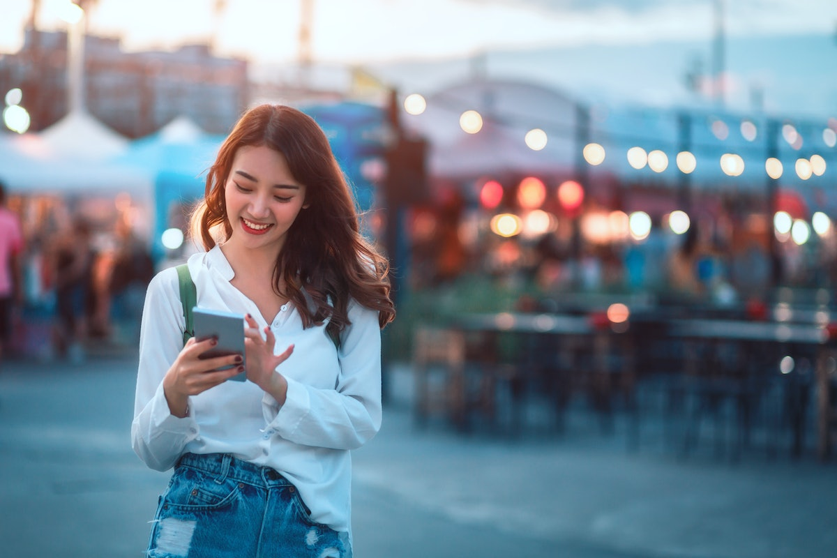 Happy young travel asian woman using mobile phone and relax on street market against light bokeh background at dusk in Bangkok, Thailand, Travel vacation city concept