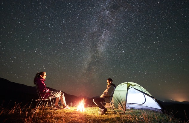 Happy couple tourists resting at summer night camping in the mountains. Smiling man and woman sittin...