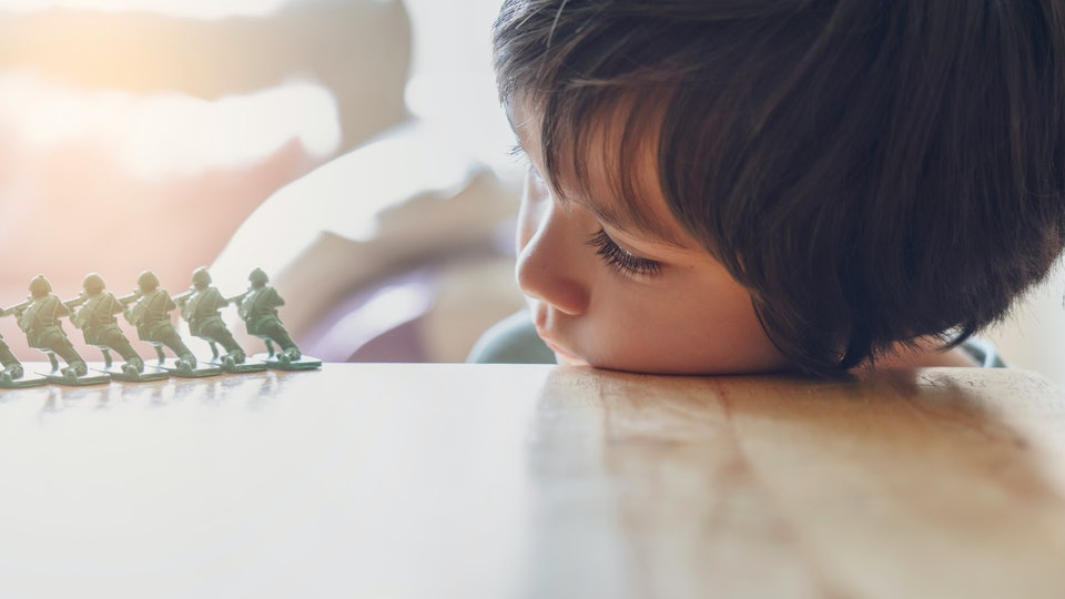 High key light portrait of lonly kid boy with sad face playing alone, Bored Child lying head donw on table looking at soldier toy with morning bright light background