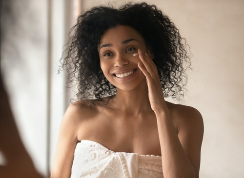 Happy african american young woman looking in mirror at bathroom, wrapped in towel after morning shower, applying moisturizing balm or cream on cure fresh clean skin. Daily hygiene skincare routine.
