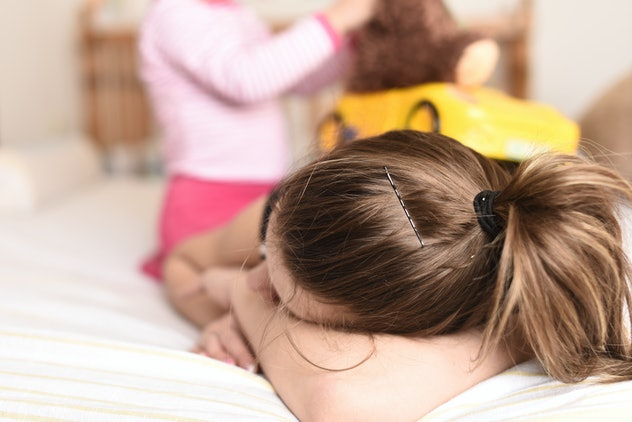 horizontal image of a young mother laying tired on the bed with her hand covering her face while her little child plays with a toy car