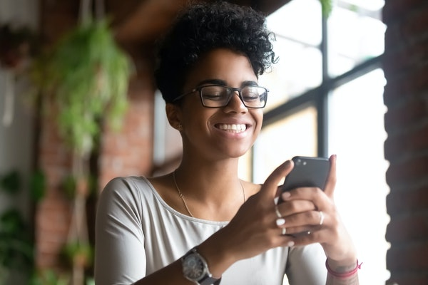 A happy Black woman smiles while texting.