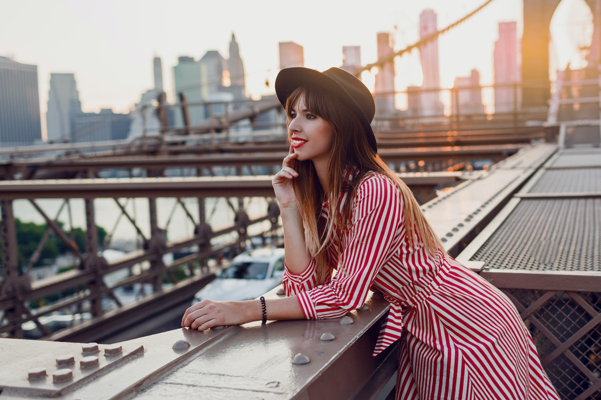 Beautiful traveling woman in red dress and stylish black hat enjoying amazing view from Brooklyn bridge in New York. Sunset colors.