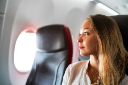 Portrait of young relaxed woman in plane looking to the window