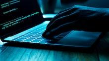 A computer programmer or hacker prints a code on a laptop keyboard to break into a secret organizati...