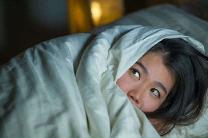 young sleepless beautiful and scared Asian Chinese woman lying on bed awake at night suffering nightmare after watching zombie horror movie in fear and stressed face expression