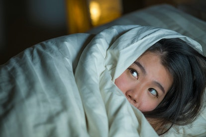 young sleepless beautiful and scared Asian Chinese woman lying on bed awake at night suffering night...