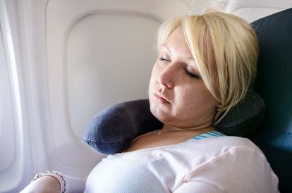 A blonde young adult woman uses a neck pillow to sleep and nap on a long airplane flight. Woman is in the window seat