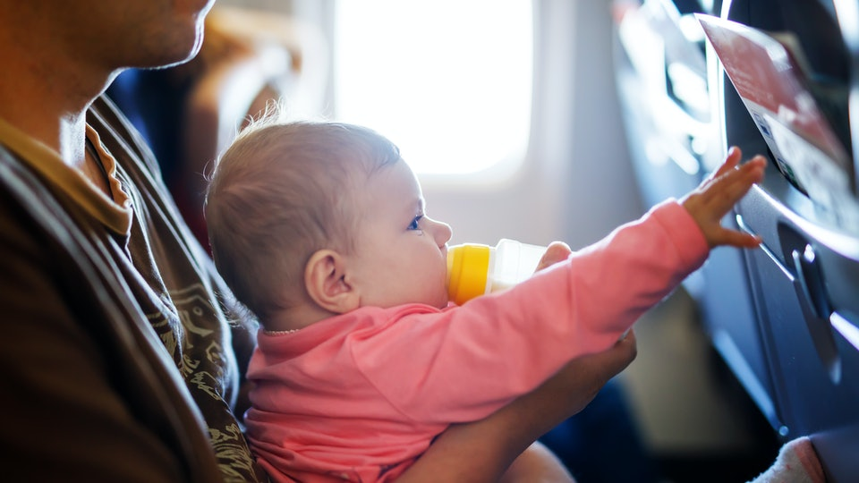 Father holding his baby daughter during flight on airplane going on vacations