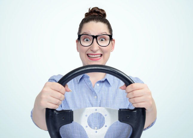Funny girl in glasses with car steering wheel, auto concept