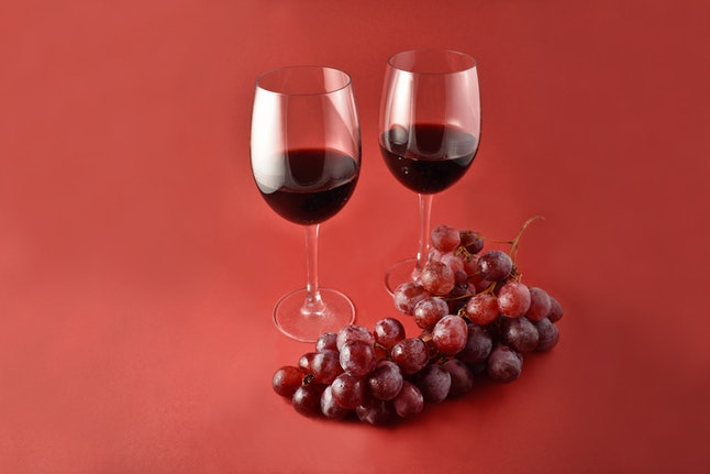 Red wine with grapes stock images. Two glasses of red wine. Red wine on a red background