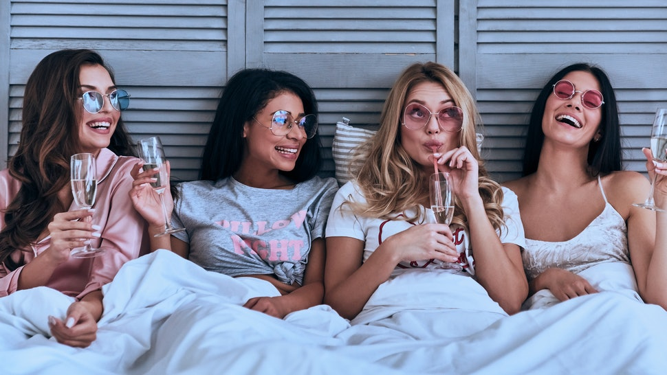 Having fun. Four attractive young women in pajamas drinking cocktails and smiling while lying in the bed