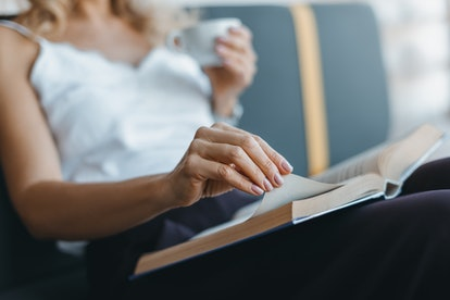 close-up partial view of woman reading book while drinking coffee