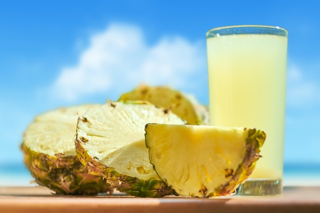 Pineapple and pineapple juice on the background of the sea.