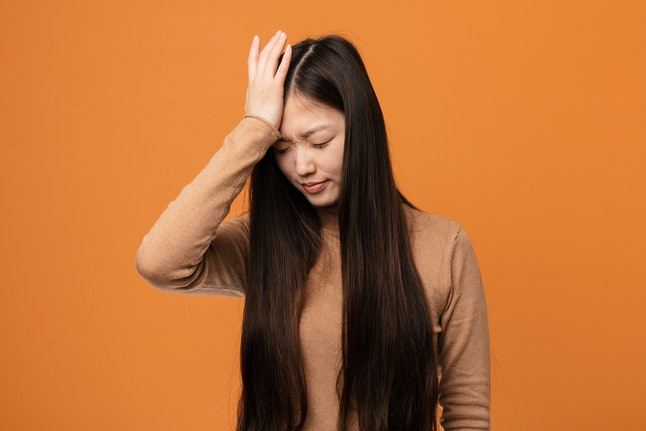 Young pretty chinese woman forgetting something, slapping forehead with palm and closing eyes.