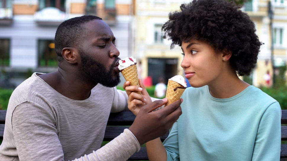 Love partners sharing ice-cream during summer date in city park, fun together