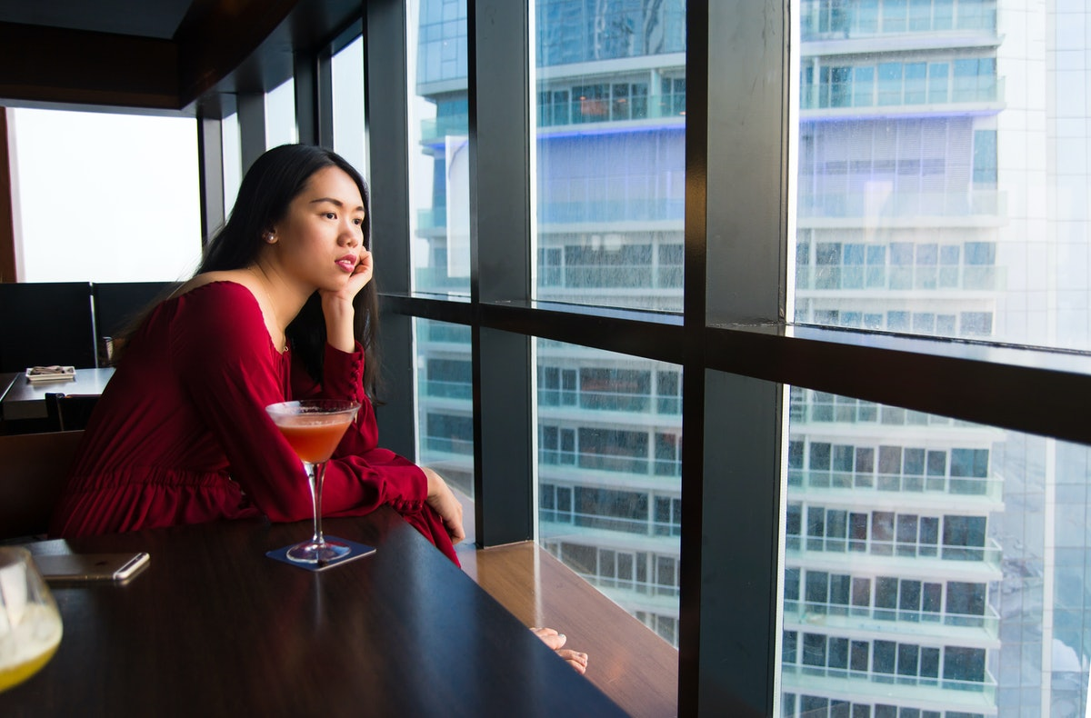 Pensive girl having a drink alone in a bar