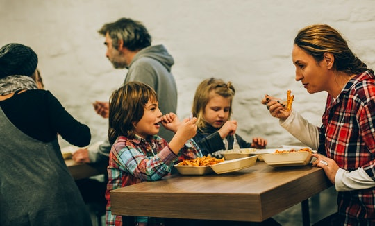 Mother with her children eats spaghetti pasta in fast food restaurant
