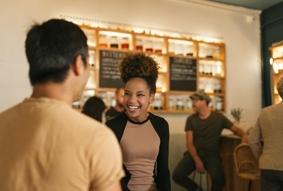Young African american woman laughing while having a good time in a trendy bar talking with a male f...