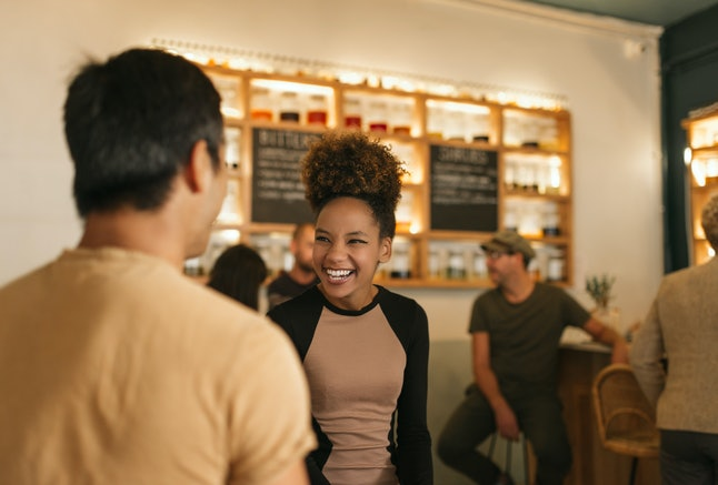 Young African american woman laughing while having a good time in a trendy bar talking with a male friend
