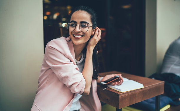 Happy female student in stylish classic spectacles laughing during time for studying in street cafeteria, positive Georgian woman in glasses using cellphone for research information for course work
