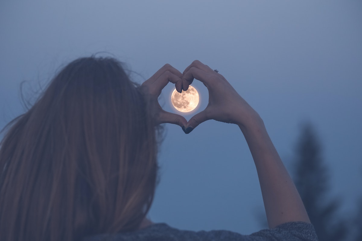 Woman making heart shape with her hands over full moon.