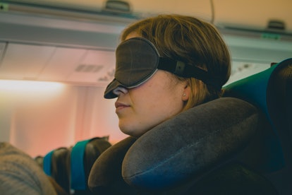 Tired caucasian blond woman with neck pillow and blindfold sleeping on a seat while traveling in a commercial airplane.