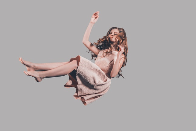 Hovering in air. Studio shot of attractive young woman hovering in air