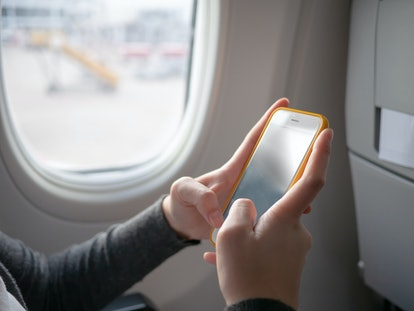 A woman passenger using  yellow mobile phone on the airplane while traveling