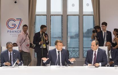 French President Emmanuel Macron, flanked by Rwanda's President Paul Kagame (L) and Egyptian Preside...