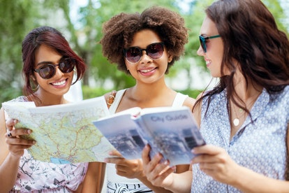 tourism, travel and friendship concept - happy tourist women or friends with map and city guide on s...