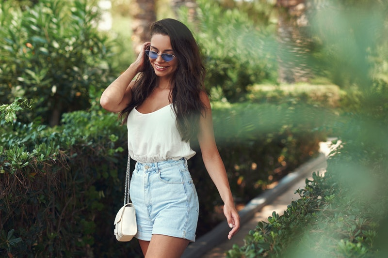 Young beautiful hipster casual dressed girl wearing shirt and jeans shorts walking between green plants in tropical garden on a sunny day